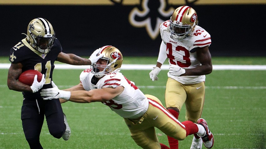 Deonte Harris of the New Orleans Saints breaks a tackle from Daniel Heim of the San Francisco 49ers.