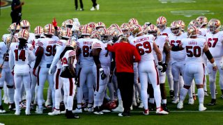 The San Francisco 49ers huddle on the field.