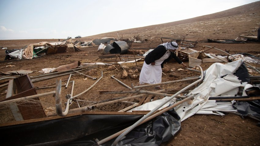 A Palestinian sifts through destroyed tents