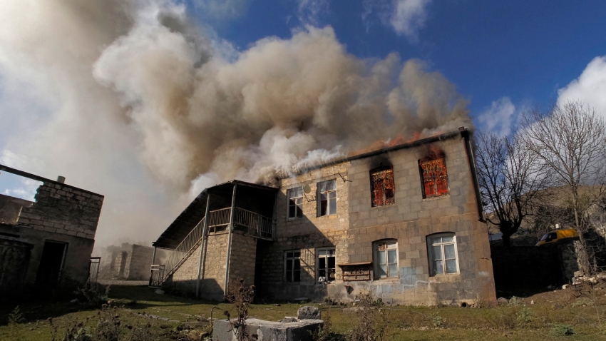 Smoke rises from a burning house in an area once occupied by Armenian forces but soon to be turned over to Azerbaijan, in Karvachar