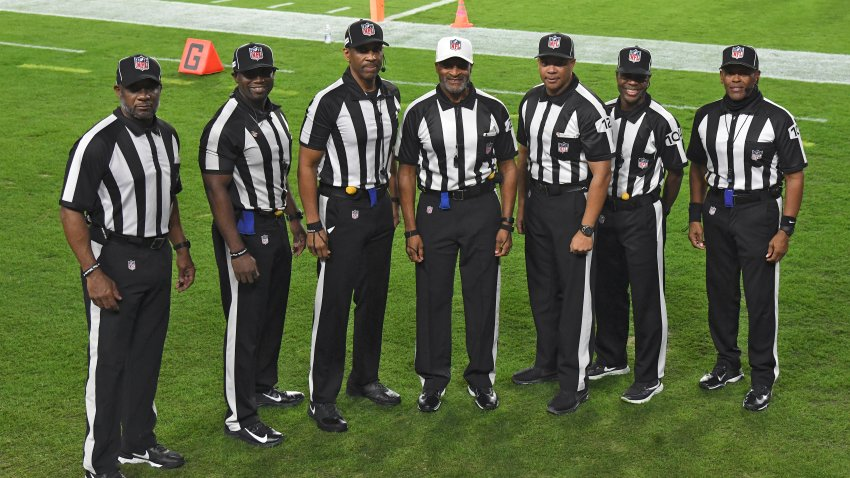 NFL officials, from left, umpire Barry Anderson, side judge Anthony Jeffries, down judge Julian Mapp, referee Jerome Boger, back judge Greg Steed, field judge Dale Shaw (104), line judge Carl Johnson (101) pose for a photo before an NFL football game between the Tampa Bay Buccaneers and the Los Angeles Rams Monday, Nov. 23, 2020, in Tampa, Fla. The game is the first in NFL history to feature an all African-American officiating crew.