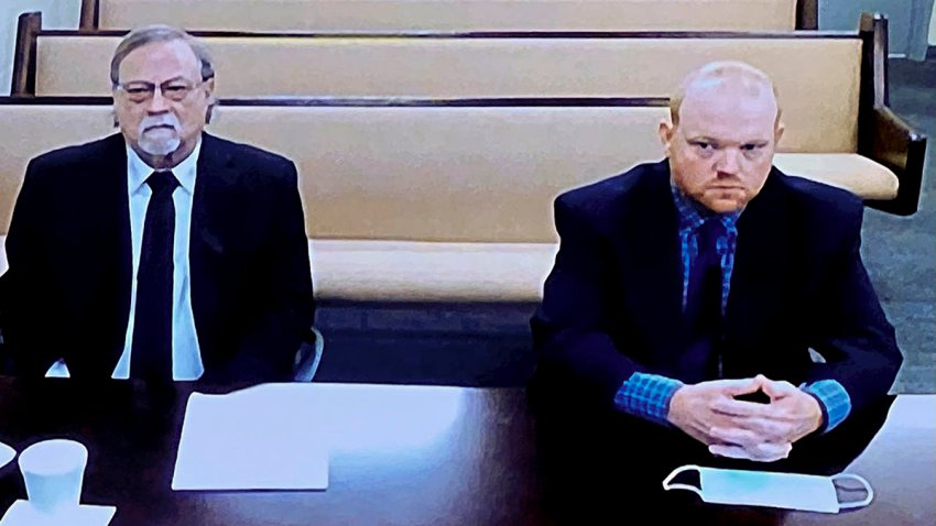 In this image made from video, from left, father and son, Gregory and Travis McMichael, accused in the Feb. 2020 shooting death of Ahmaud Arbery in Georgia, listen via closed circuit TV in the Glynn County Detention center in Brunswick, Ga., Nov. 12.