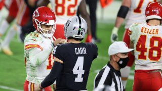 Quarterbacks Patrick Mahomes of the Kansas City Chiefs and Derek Carr of the Las Vegas Raiders fist bump.