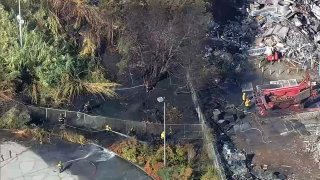 Crews work at the scene of a fire in East Oakland.