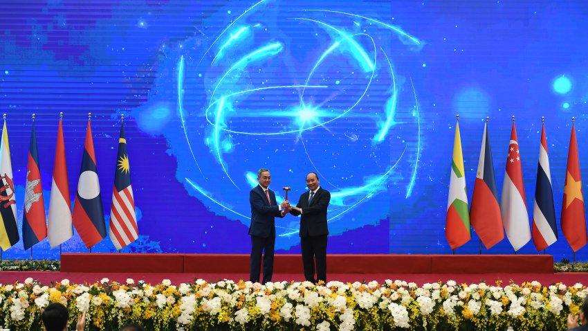 Vietnam's Prime Minister Nguyen Xuan Phuc (R) hands over the ASEAN gavel, a symbol of Association of Southeast Asian Nations (ASEAN) chairmanship, to Brunei's ambassador to Vietnam Pengiran Haji Sahari Bin Pengiran Salleh (L) during the closing ceremony of ASEAN summit being held online in Hanoi on November 15, 2020.