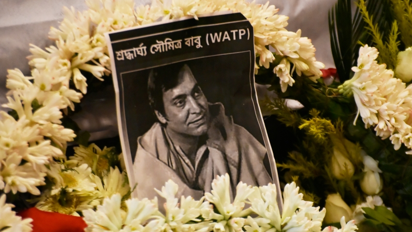 Flowers surround a photo of Indian actor Soumitra Chatterjee