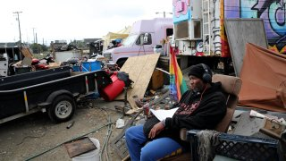 Larry Coke sits in his recliner at the Wood Street encampment in Oakland.