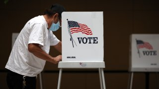 In this Oct. 13, 2020, file photo, a voter fills out his ballot while early voting at the Santa Clara County registrar of voters office in San Jose, California.