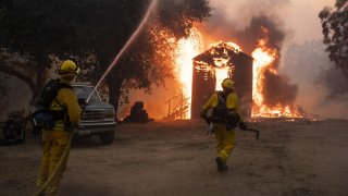 Firefighters work to prevent the fire from spreading during the Zogg fire.