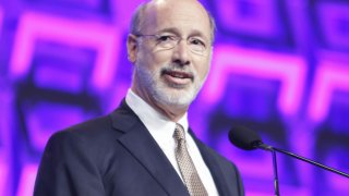 Governor of Pennsylvania Tom Wolf stands at a podium in front of a microphone and speaks on stage