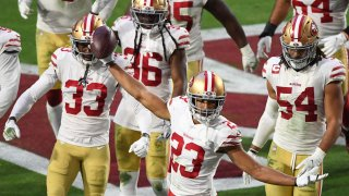 Cornerback Ahkello Witherspoon of the San Francisco 49ers celebrates with teammates after intercepting the ball.