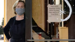 Brenda Luntey, poses for a photo by a sign advising customers to wear face masks that is posted on the door of the San Francisco Deli in Redding, Calif., Thursday, Dec. 3, 2020.