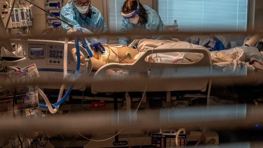 Phlebotomist lab assistant Jennifer Cukati, right, and Registered Nurse Carina Klescewski, left, care for a COVID-19 patient inside the Sutter Roseville Medical Center ICU in Roseville, Calif., on Tuesday, Dec. 22, 2020.