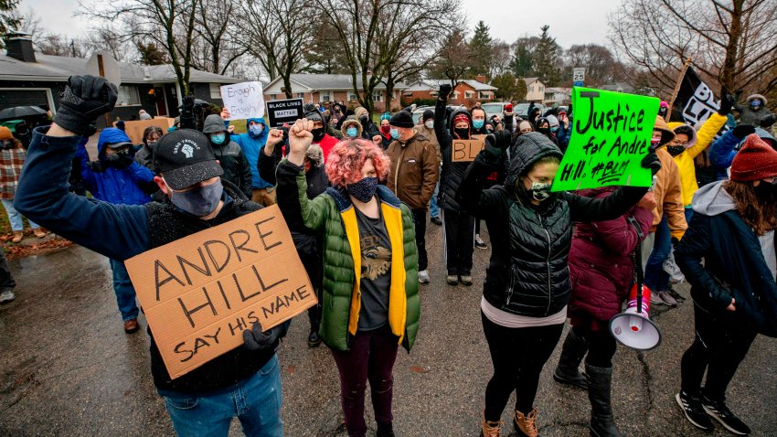 Protesters raise their fists and observe a moment of silence during a demonstration against the police killing of Andre Hill in the neighborhood where Hill was shot, in Columbus, Ohio, on December 24, 2020.