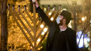 A member of Chabad of Midtown lights the first candle of Hanukkah in the Hudson Yards on December 10, 2020 in New York City