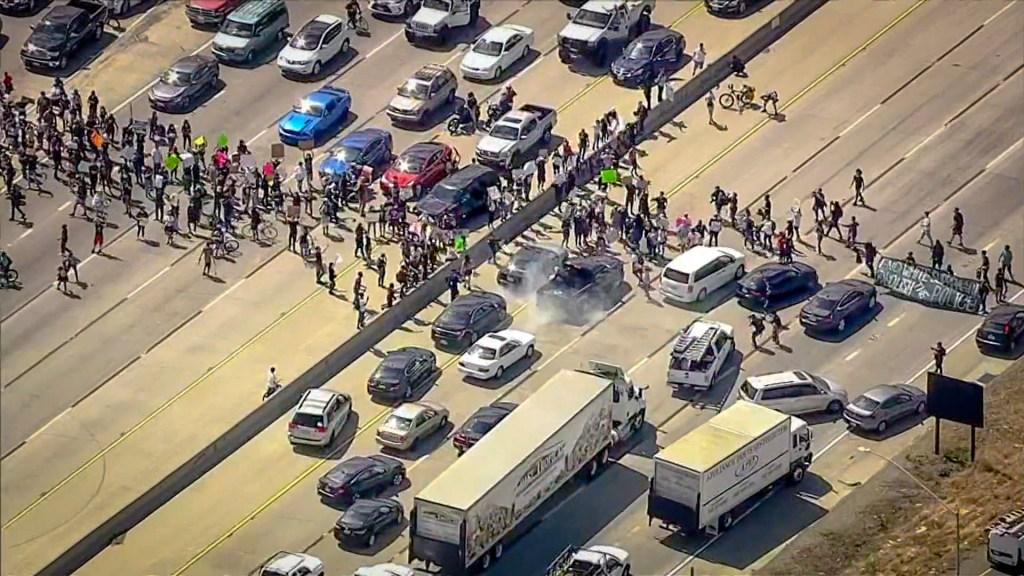 protesters swarm onto a freeway, blocking traffic