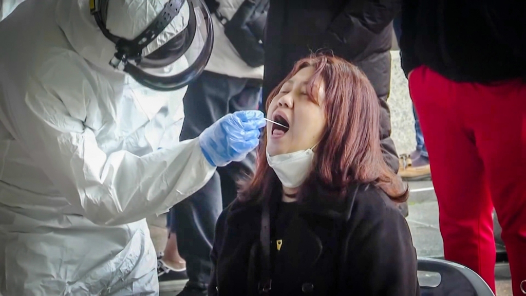 a person in full hazmat gear swabs the mouth of a seated woman