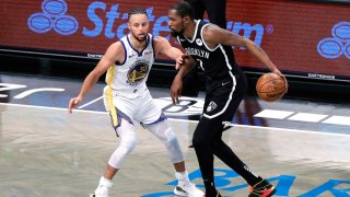 Kevin Durant of the Brooklyn Nets dribbles against Stephen Curry of the Golden State Warriors.
