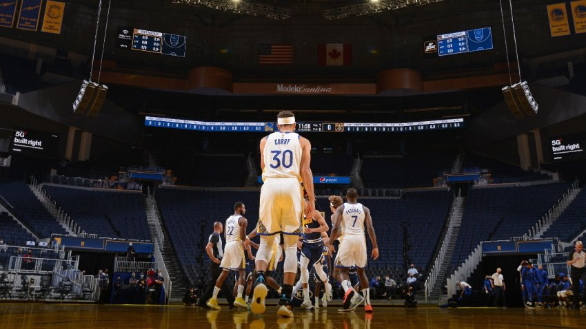Stephen Curry of the Golden State Warriors stands on the court during a preseason game.