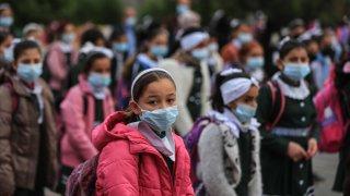 Children standing wearing masks.