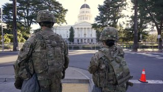 Members of the California National Guard walk past the California state Capitol in Sacramento, Calif., Wednesday, Jan. 20, 2021.