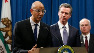 In this March 12, 2020, file photo Dr. Mark Ghaly, secretary of the California Health and Human Services, discusses the coronavirus as Gov. Gavin Newsom, center, listens at a news conference in Sacramento, Calif.