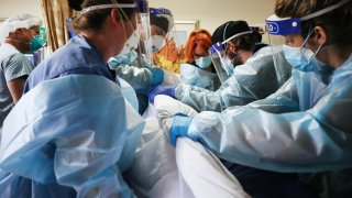 Clinicians re-position a COVID-19 patient into the supine position.