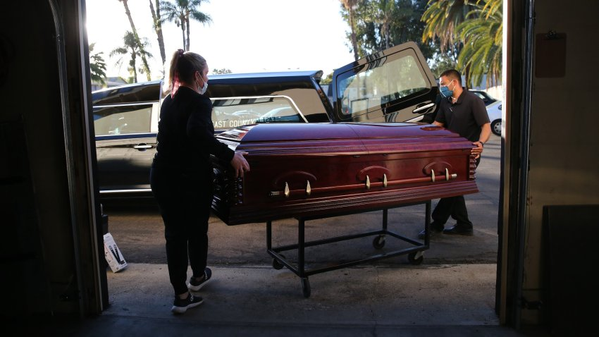 Embalmer and funeral director Kristy Oliver and funeral attendant Sam Deras load the casket of a person who died after contracting COVID-19.