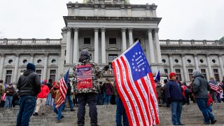 A protester holds a Betsy Ross Three Percent flag during a demonstration