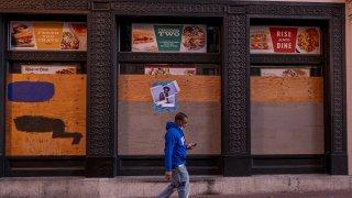 Un hombre camina frente a un restaurante cerrado en Market Street, en San Francisco.
