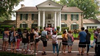 fans wait in line outside Graceland, Elvis Presley's Memphis home, in Memphis, Tenn.