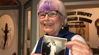 Nurse practitioner Sigrid Stokes, 76, holds a photograph of her mother talking to Shirley Temple, at the Salinas Valley Memorial Hospital in Salinas, California, Feb. 3, 2021.