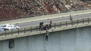 This drone photo provided by the Tuolumne County Sheriff shows personnel from multiple agencies grabbing a man who is attempting to jump from the Parrotts Ferry Bridge, Monday, Feb. 8, 2021. Authorities say the man trying to jump off the bridge was saved when a sheriff's deputy gripped his arm as the man dangled 150 feet above the waters of New Melones Lake in the Sierra Nevada. He was taken to a hospital for a mental evaluation