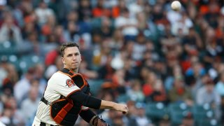 Catcher Buster Posey of the San Francisco Giants fields a bunt and throws to first base.