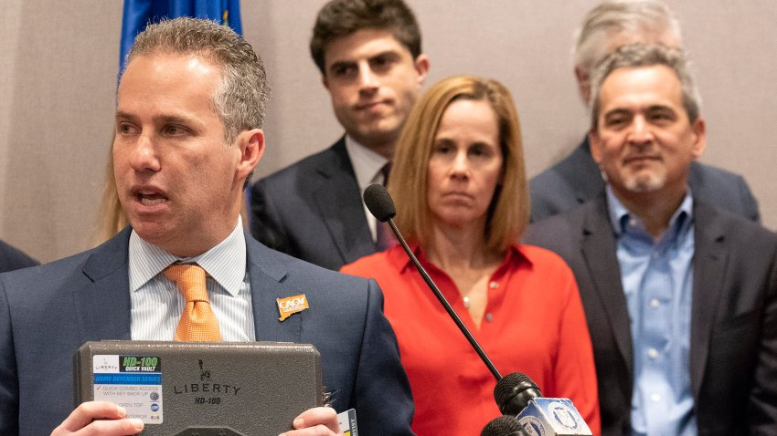 """Jeremy Stein, executive director of CT Against Gun Violence, displays a gun safe or vault during a news conference on March 11, 2019, at the Legislative Office Building in Hartford, Conn. Michael Song, at right, and his wife, Kristen, center, along with legislators and gun-safety advocates are pushing for """"Ethan's Law,"""" to create state requirements for safe gun storage."""