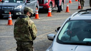 Servicemen coordinate with people in their cars as they line up and wait to be vaccinated