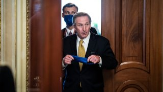 Michael van der Veen, lawyer in former President Donald Trump's impeachment trial, raises a blue face mask toward his face as he walks between two wooden doors. A man walks behind him, already wearing a face mask.