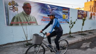 In this Feb. 27, 2021, file photo, a boy cycles past a poster welcoming Pope Francis, who is expected visit Iraq in March, hanging on the wall of the Chaldean Catholic Church of St. Joseph in the capital Baghdad.