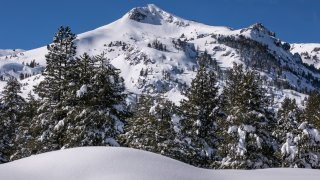 The mountains and trees along Highway 50 are covered in snow.