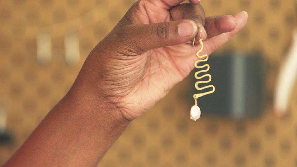 Candice Cox holds up a newly-made earring in her Oakland shop, Candid Art.