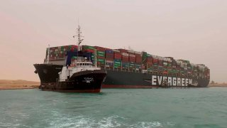 In this photo released by the Suez Canal Authority, a boat navigates in front of a massive cargo ship, named the Ever Green, rear, sits grounded Wednesday, March 24, 2021, after it turned sideways in Egypt's Suez Canal, blocking traffic in a crucial East-West waterway for global shipping. An investigation into the incident is underway after the ship was freed on March 29, 2021.