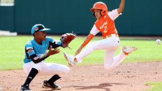 SOUTH WILLIAMSPORT, PENNSYLVANIA - AUGUST 25: Alton Shorts #2 of the Southwest Region team from River Ridge Louisiana slides safely into second base in front of Curley Martha #12 of the Caribbean Region team from Willemstad, Curacao during the Championship Game of the Little League World Series at Lamade Stadium on August 25, 2019 in South Williamsport, Pennsylvania.