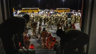 U.S. Army troops from the 10th Mountain Division collect their duffels after returning from a 9-month deployment in Afghanistan on December 08, 2020 in Fort Drum, New York.