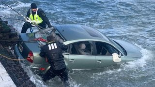 Crews pull a car out of the San Francisco Bay.