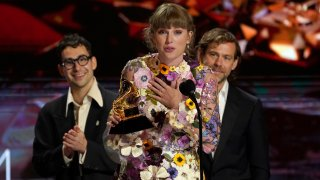 """Taylor Swift accepts the award for album of the year for """"Folklore""""at the 63rd annual Grammy Awards at the Los Angeles Convention Center on Sunday, March 14, 2021. In background Jack Antonoff, left, and Aaron Dessner."""