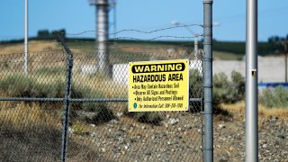 In this Wednesday, Aug. 14, 2019 photo, a sign at the Hanford Nuclear Reservation warns of possible hazards in the soil there along the Columbia River near Richland, Wash. Washington state officials are worried that the Trump administration wants to reclassify millions of gallons of wastewater at Hanford from high-level radioactive to low-level, which could reduce cleanup standards and cut costs.