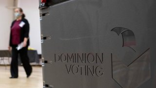A worker passes a Dominion Voting ballot scanner while setting up a polling location at an elementary school in Gwinnett County, Ga., outside of Atlanta on Monday, Jan. 4, 2021, in advance of the Senate runoff election.