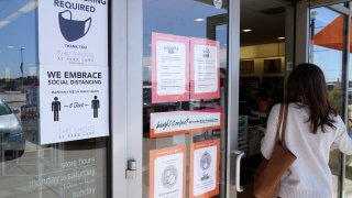 FILE - A customer enters a store with a face mask required sign displayed in Dallas, in this Tuesday, March 2, 2021, file photo. Although nearly a fifth of U.S. states don't require people to wear masks to protect against COVID-19, some businesses are requiring employees and customers to be masked on their premises.