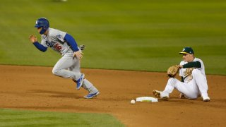 Will Smith of the Los Angeles Dodgers runs to third base after colliding with Matt Chapman of the Oakland Athletics.
