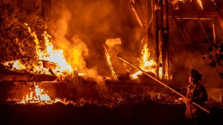 A firefighter tends to a structure lost during the Kincade fire off Highway 128, east of Healdsburg, California on October 29, 2019.